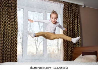 child funny home. Cheerful boy jumping in bedroom on bed. Little kid of 6 years old happily plays morning in room. mischievous childhood.