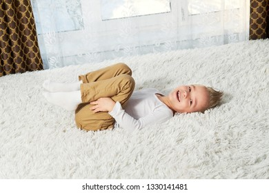 child funny home. Happy little boy blond lying on soft bedspread bed, top view. Little kid laughing while looking at camera.