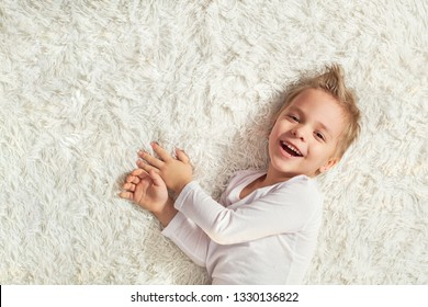 child funny home. Portrait happy little blond boy lying on soft bedspread bed, top view. Little kid laughing while looking at camera. copy space. top view