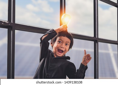 Child with future of alternative energy and sustainable energy. Funny Asian boys hold a light bulb that shines in their hands at Solar panel, photovoltaic. Eco-Friendly and Pure energy Concept