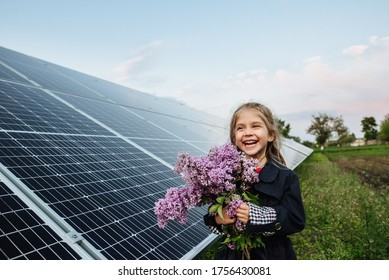 A child with a future of alternative energy and sustainable energy. The child holds flowers on a background of solar panels, photovoltaic. Environmental friendliness and clean energy concept.
