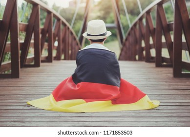 child with german flag on wooden bridge