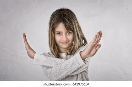child gestures x crossing arms, light background