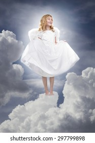 Child or girl angel wearing a white dress standing on fluffy clouds in the sky