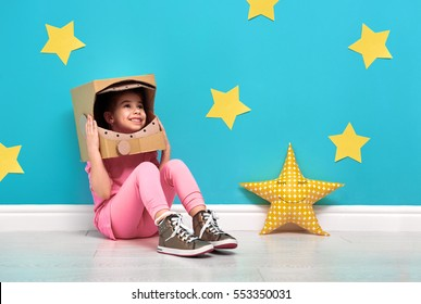 Child girl in an astronaut costume is playing and dreaming of becoming a spacemen. Portrait of funny kid on a background of bright blue wall with yellow stars.