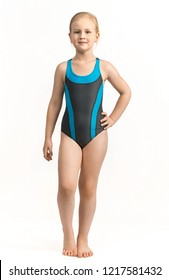 Child, girl athlete stands in a sports swimsuit full face on a white background. Smile and joy on the face.
