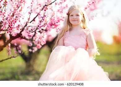 Child girl in blooming garden with pink flowers
