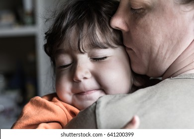 Child girl with both hands hugging his mother.