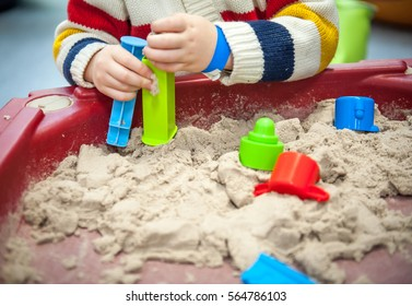 Child girl boy mould with kinetic sand in play school or daycare Kinetic Sand Heap Indoor Table Game And Creativity. Sand With Child Toys For Indoor Children Creativity Games Or Beach Games Concept.