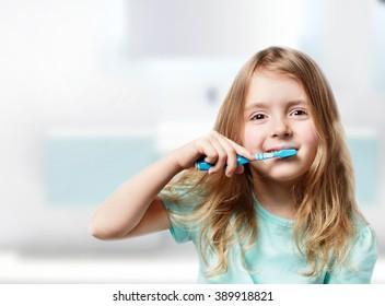 Child girl brushing teeth empty space background.