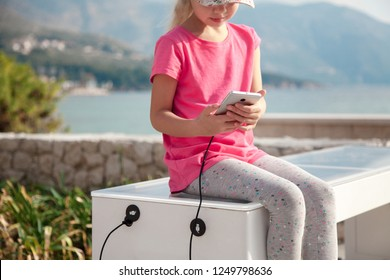 Child girl charges mobile phone via USB outdoors. Kid is sitting on bench with solar panel by sea. Public charging on town street. Concept of modern technology, ecology, renewable energy.