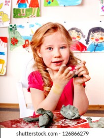 Child girl with clay in play room. Preschool.