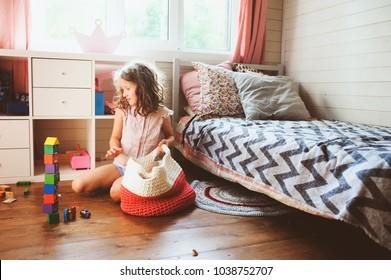 Kindermädchen, die ihr Zimmer putzt und Holzspielzeug in Stricktaschen organisieren. Konzept für Hausarbeit und Hilfe