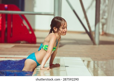 Child girl climbs on the edge of the pool, outdoor