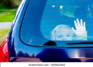 Child girl closed alone in the back of a parking car on a hot day. Concept image of danger of overheating in car for young children in the summer