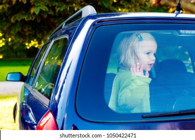 Child girl closed in the back of a car on a hot day. Concept image of danger of overheating in car for young children in the summer