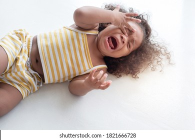 child girl crying and shouting with tantrum lying on the floor at home