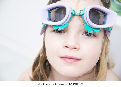 Child girl with diving goggles dive in the bath with foam