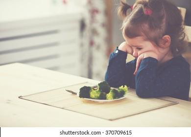 child girl does not like  eat vegetables