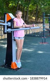 child girl doing outdoor exercise. little girl gymnast is actively involved in sports outside. girl on the playground in park