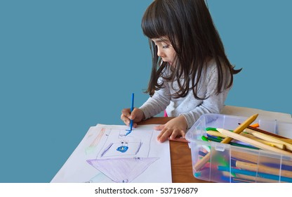 child girl drawing with colors pencils. isolated blue background
