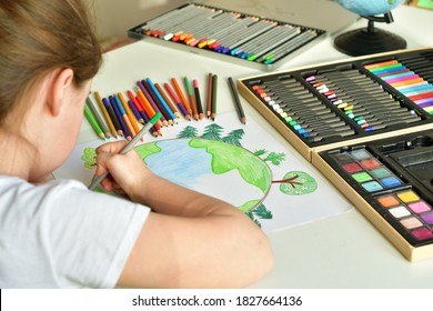 Child girl draws planet for earth day. Protection of enviroment, Save our planet. Concept of art learning and education, love earth , save world and unity.Ecology concept.Selective focus