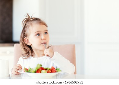 Child girl eating fresh raw vegetables vitamin salad in white kitchen background and thoughtfully looks at the empty copy space.Healthy nutrition food for children. Place for text for advertising.
