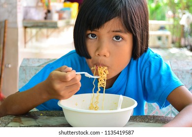Child girl eating Instant noodles. Concept of Instant noodles may cause health problems in child.