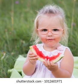Child girl eating slice watermelon on green blur background.