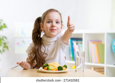 child girl eats healthy food showing thumb up at kindergarten