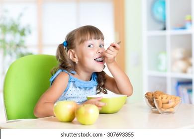 Child girl eats tasty breakfast in nursery