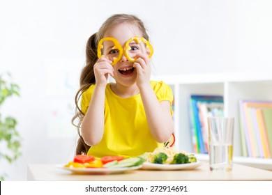 child girl eats vegan food having fun in kindergarten