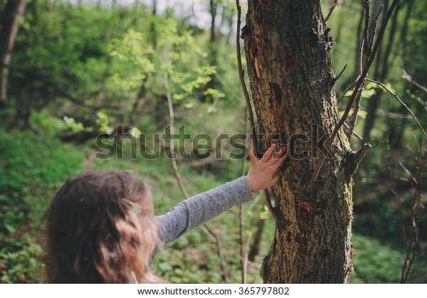 child girl exploring nature in early spring forest. Kids learning to love nature. Teaching children about seasons changing. Warm weather.