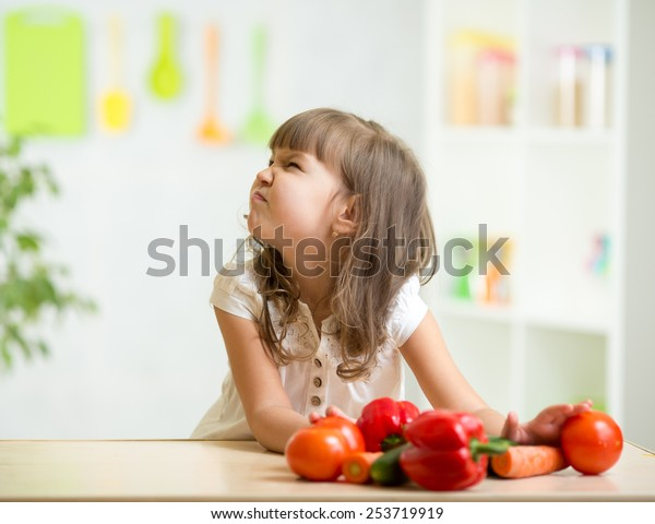 child girl with expression of disgust against vegetables