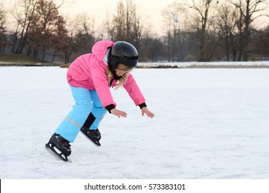 Child girl falling down on ice in snowy park during winter holidays. Wearing safety helmet. Winter children activities.