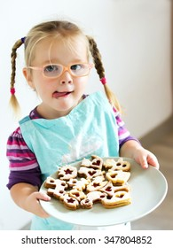 child girl with glasses have protruding tongue and hold plate with xmas cookies