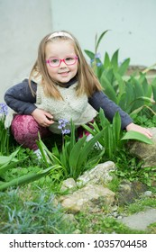Child girl with glasses sitting in the garden