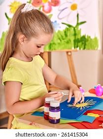 Child girl  glue paper in preschool.