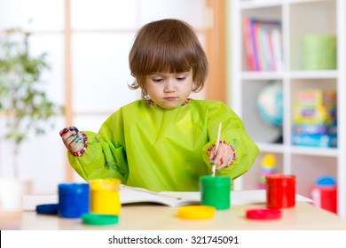 Child girl with hands painted color paints weared apron in playschool