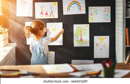 child girl hanging her drawings on the wall - Shutterstock ID 666421609