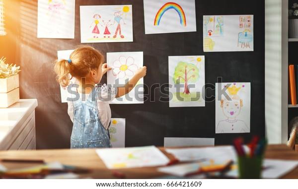 壁に絵を掛けている少女