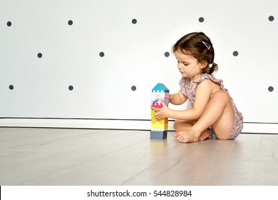 Child girl having fun and build a house of wooden construction blocks. Toddler playing on the floor. Developing toys. Early learning.