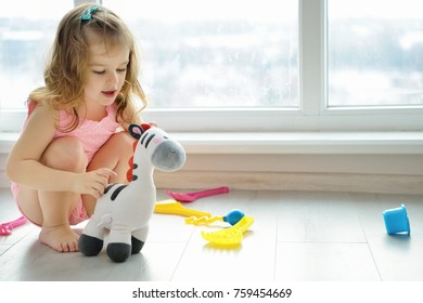Child girl having fun and play. Toddler playing on the floor. Developing toys. Early learning.
