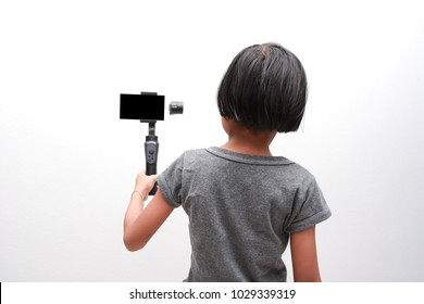 Child girl holding Gimbal (Smartphone Gimbal Stabilizer) for recording footage. Child and Technology concepts.