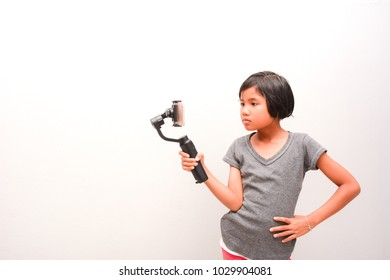 Child girl holding Stabilizer for recording footage. Child and Technology concepts.