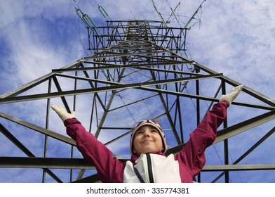 Child girl holds his hands up near high-voltage power line on the blue sky background.