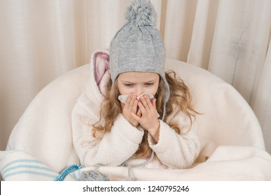 Child girl at home in chair with warm knitted hat woolen blanket sneezes in handkerchief. Season autumn winter colds.