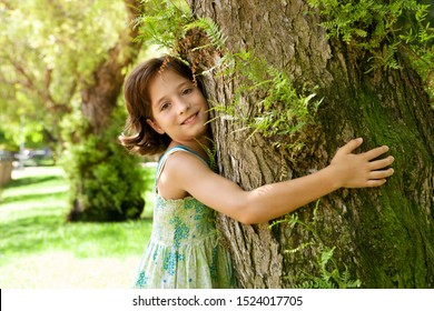 Child girl hugging mature organic textured tree trunk, sunny forest park, looking smiling, love nature. Kid caring and protecting organic eco climate change resources. Future healthy wellbeing planet.