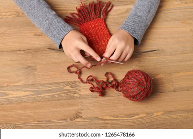 Child girl is learning to knit a scarf. Red wool yarn is on the wooden table. Hand closeup.