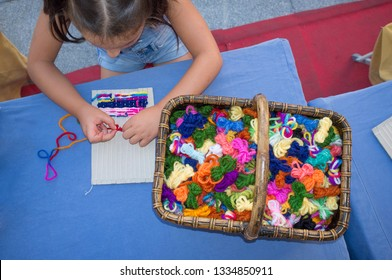 Child girl learning to use cardboard weaving loom. Manual arts workshop for children
